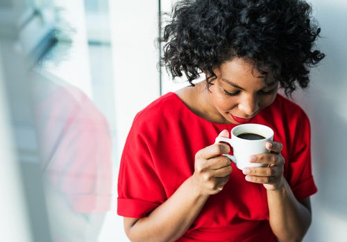 A Black woman wearing a red shirt smelling a fresh cup of black coffee.