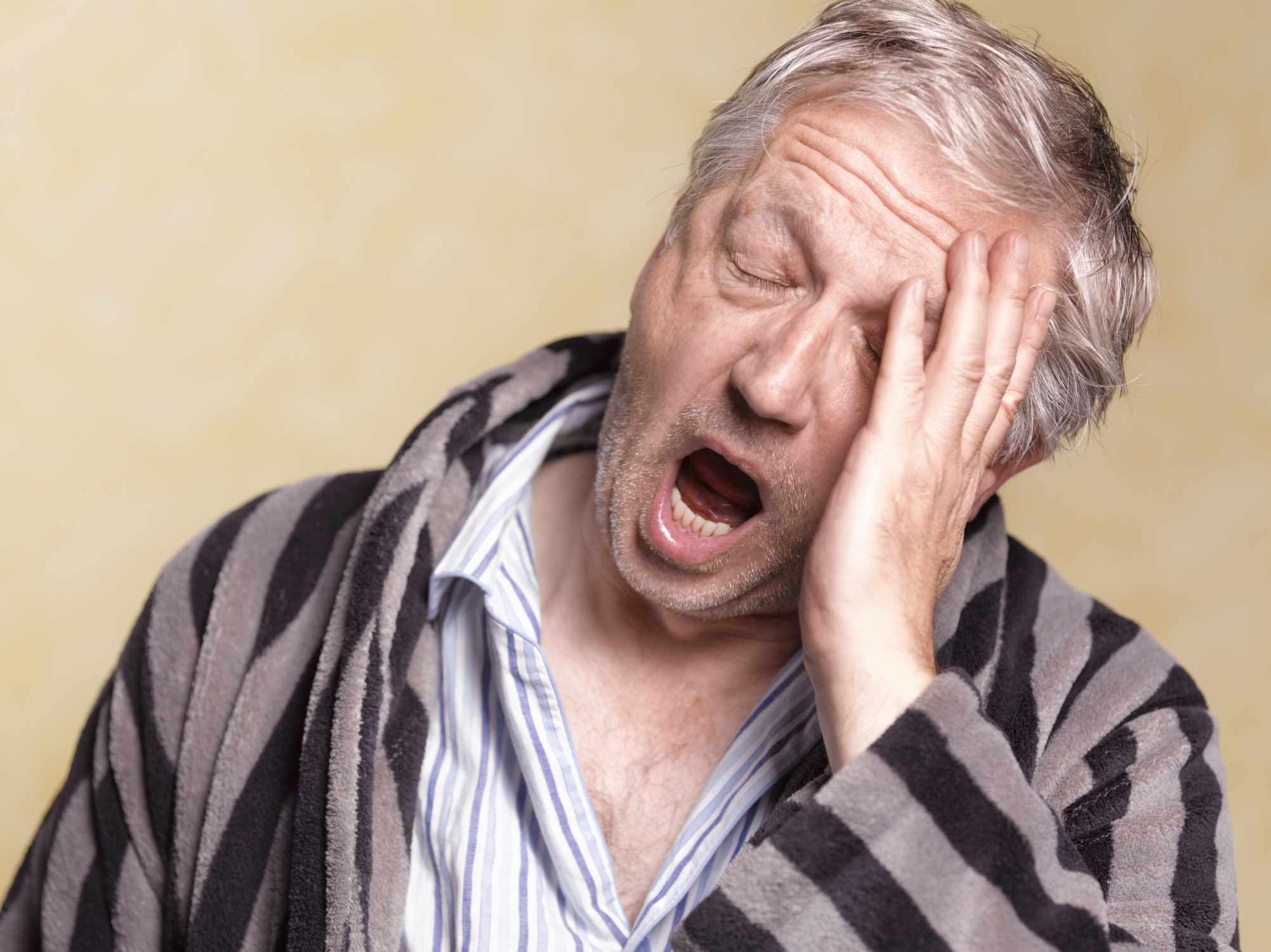 Older man yawning in a robe and pajamas