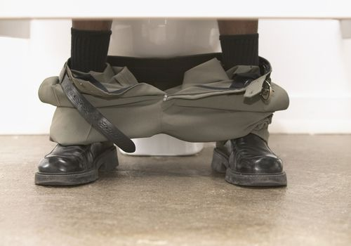 Man on toilet with pants around ankles