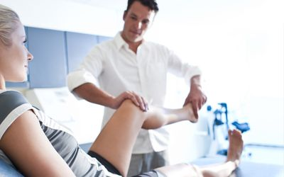 physical therapist working with a woman's knee