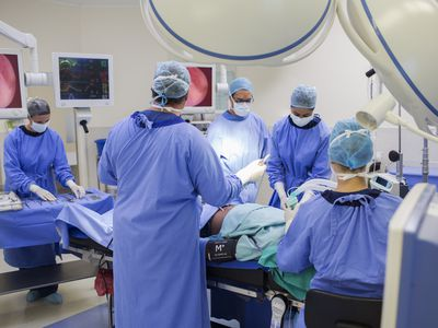 Team of doctors performing surgery in operating theater