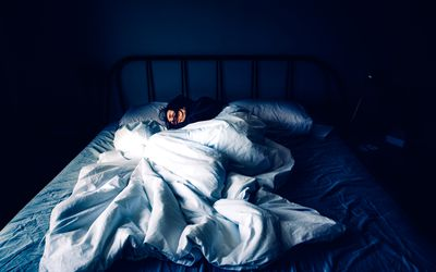 A woman sleeping in bed at night with blankets askew