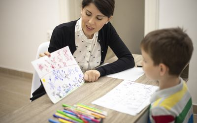Therapist talking to little boy with drawing