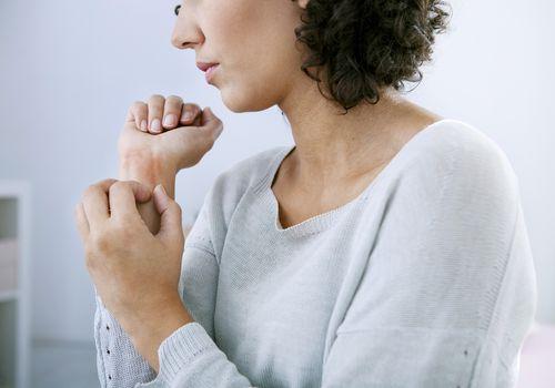 Woman scratching her wrist