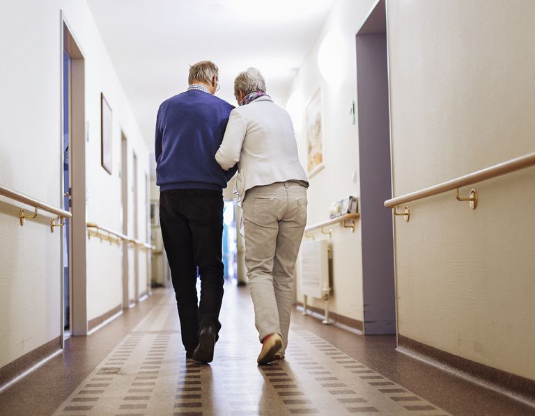 two people walking down nursing home hallway
