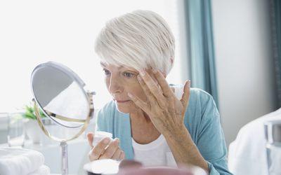 older woman applying eye cream