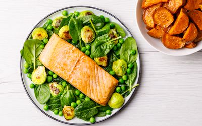 Plate of spinach, peas, brussel sprouts, and salmon with a side of sweet potatoes