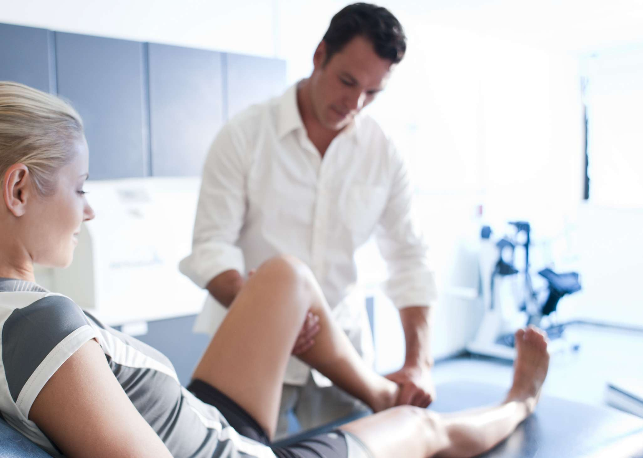 Physical therapist works on woman's lower leg
