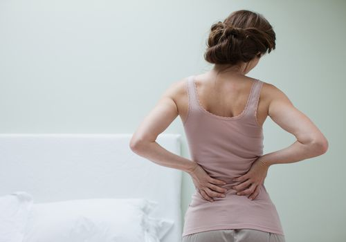 Woman holding her back, having lower back pain from PID