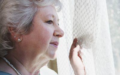 Elderly woman looking out window