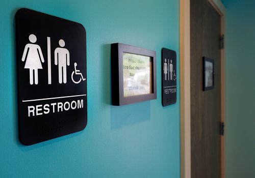 Restroom signs on a blue wall