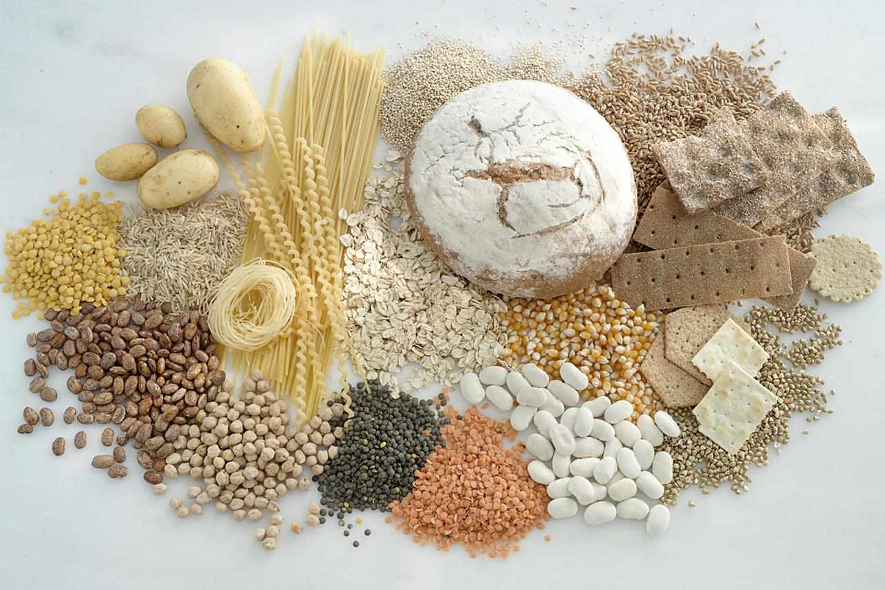 Several carbohydrate-heavy foods on a white background, including bread, wheat and crackers