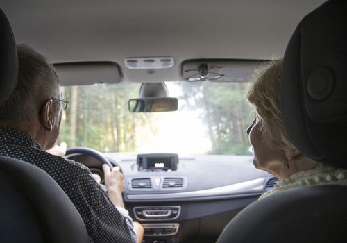 Senior couple driving in car