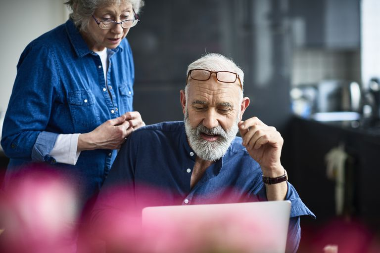 Senior man and woman looking at laptop screen