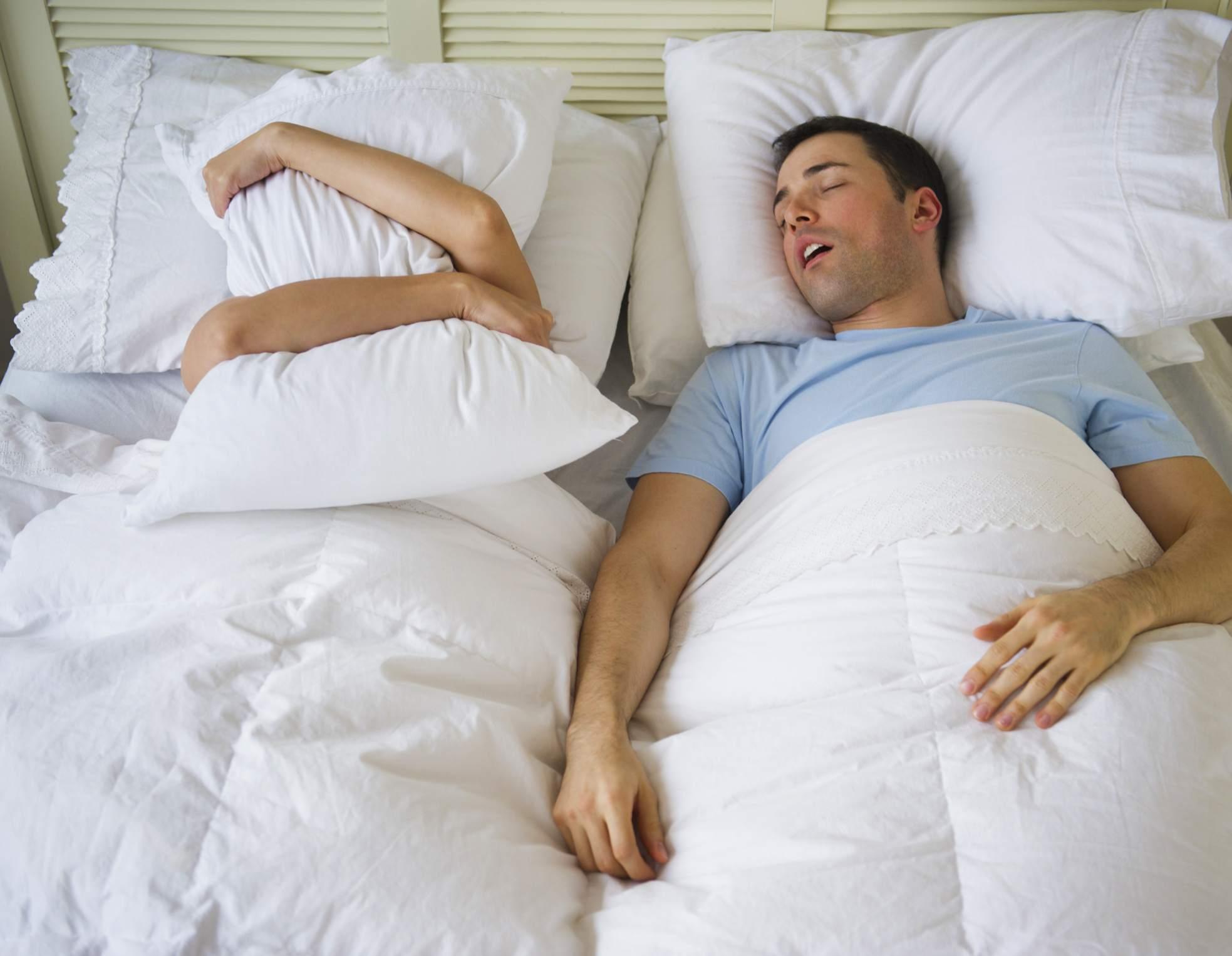 Man snoring loudly while his partner covers her head in a pillow
