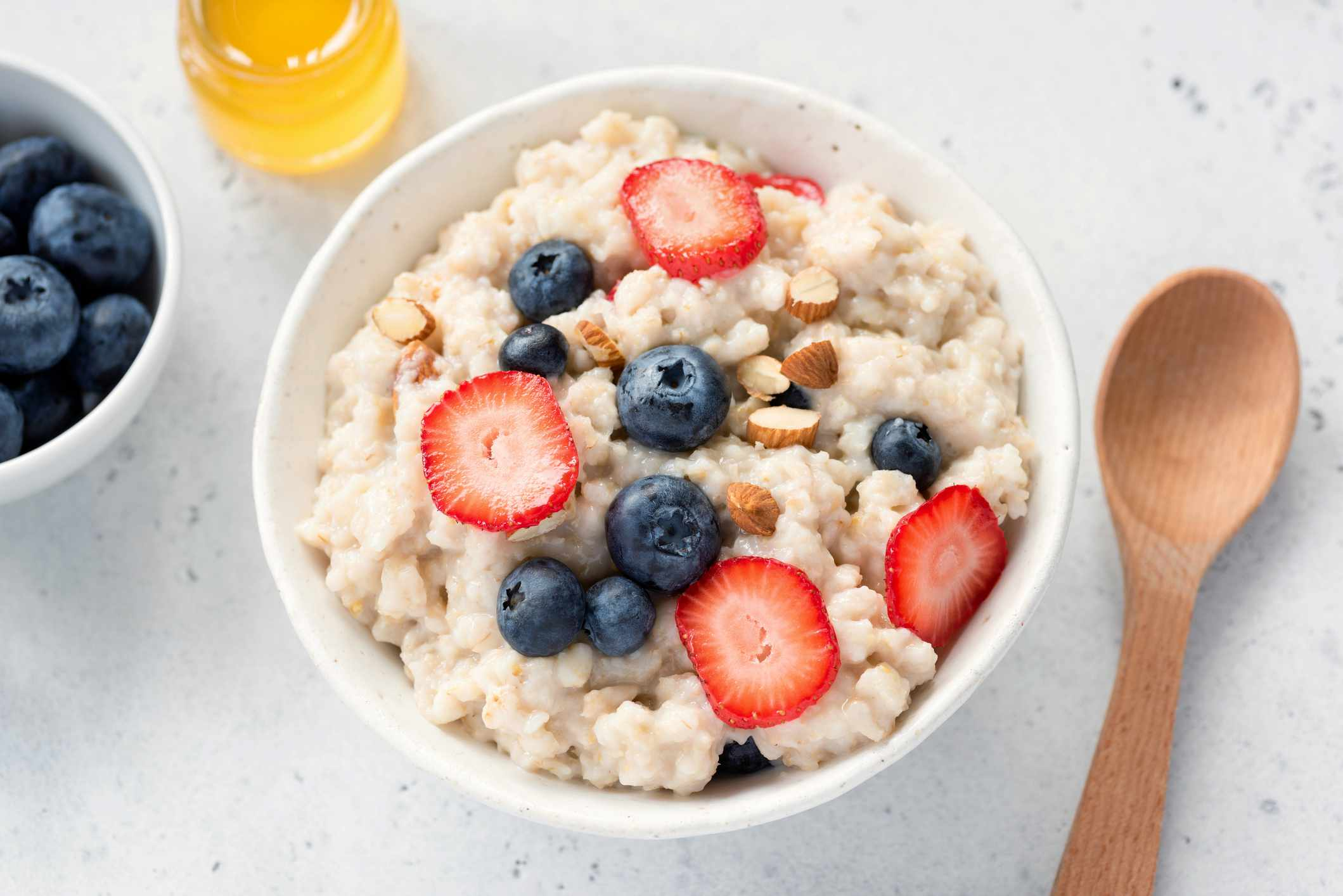 A bowel of oatmeal topped with blueberries, strawberries, and almonds.