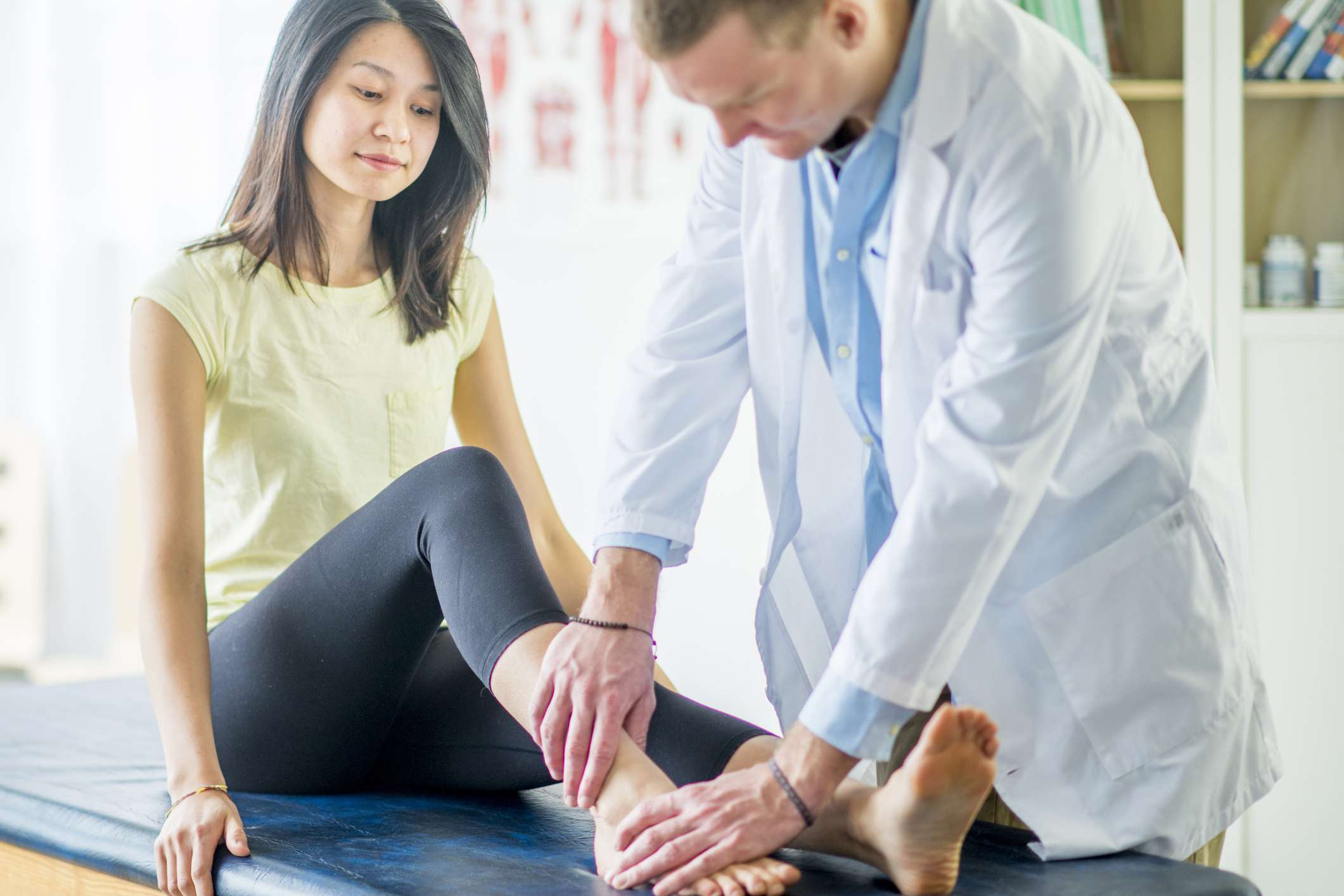 Woman getting her ankle checked by a doctor
