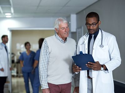 Doctor looking at clipboard with patient