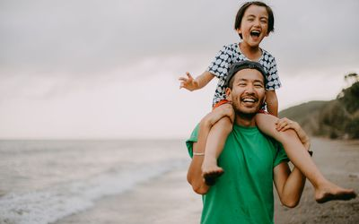 Cheerful father carrying his daughter on shoulders on beach