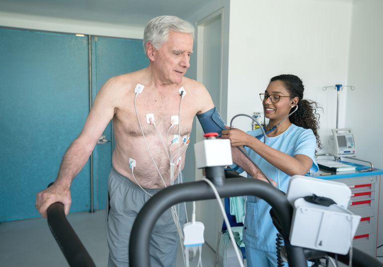 Nurse checking a senior man's blood pressure as he undergoes a stress test