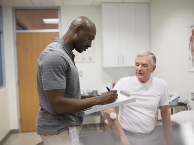A physical therapist taking notes with his patient