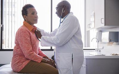 Smiling female doctor examining senior patient in hospital