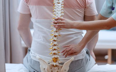 Caucasian nurse holding spine model against the patients backs. Clinic interior. - stock photo