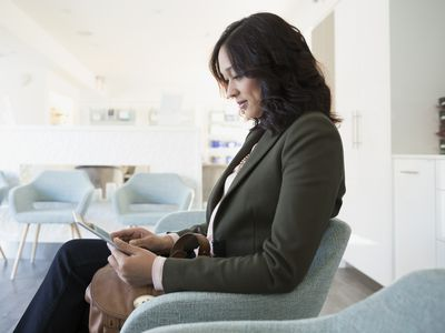 Woman using digital tablet waiting in clinic lobby