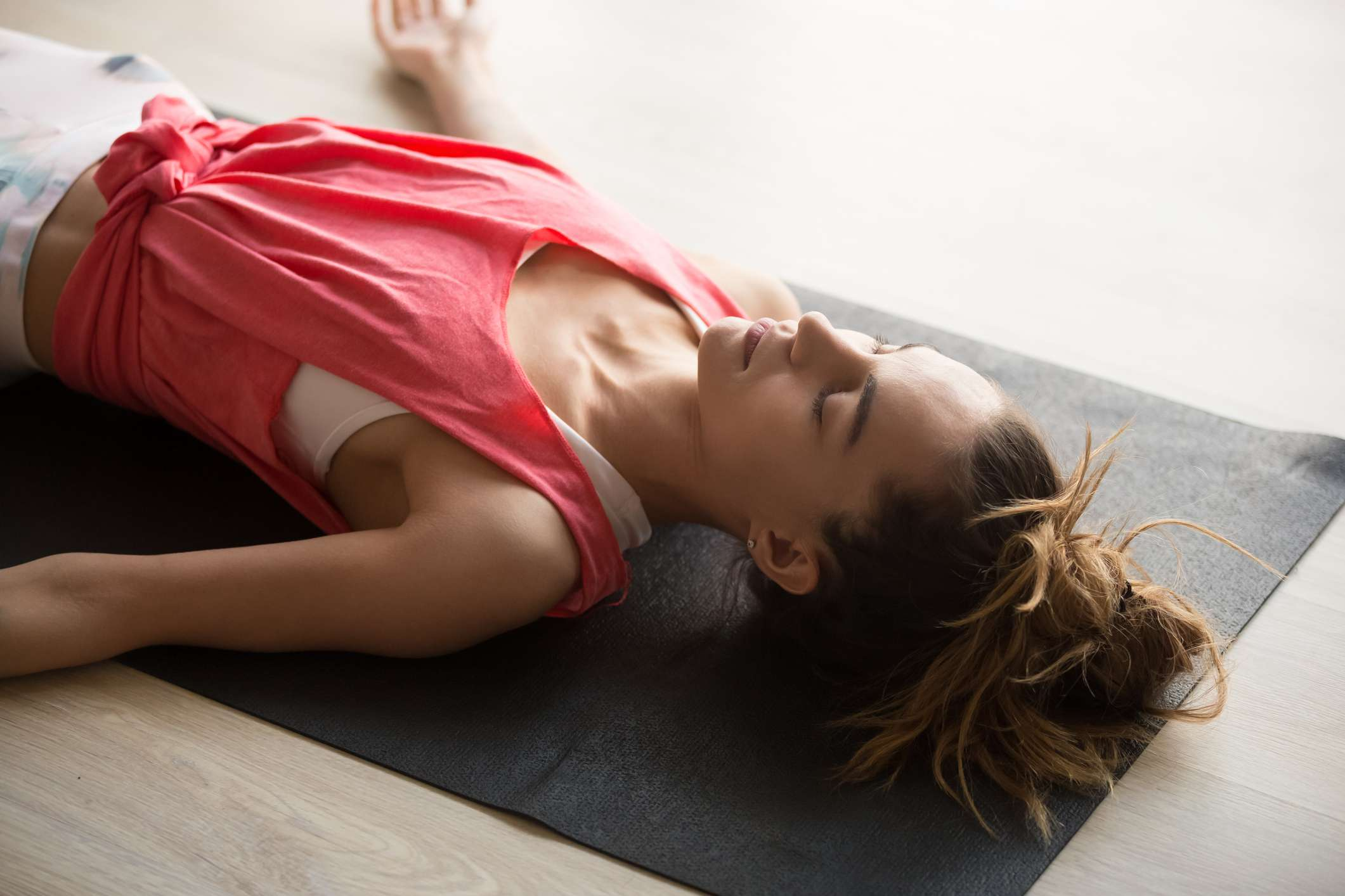 A white woman with a pink-red tank top laying on a gray mat with her eyes closed.