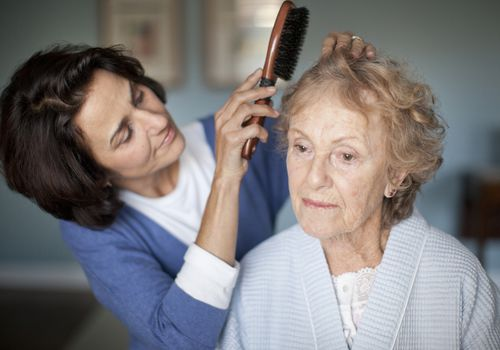 Woman brushing an elderly woman's hair