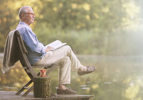 An older man reading his book on a dock