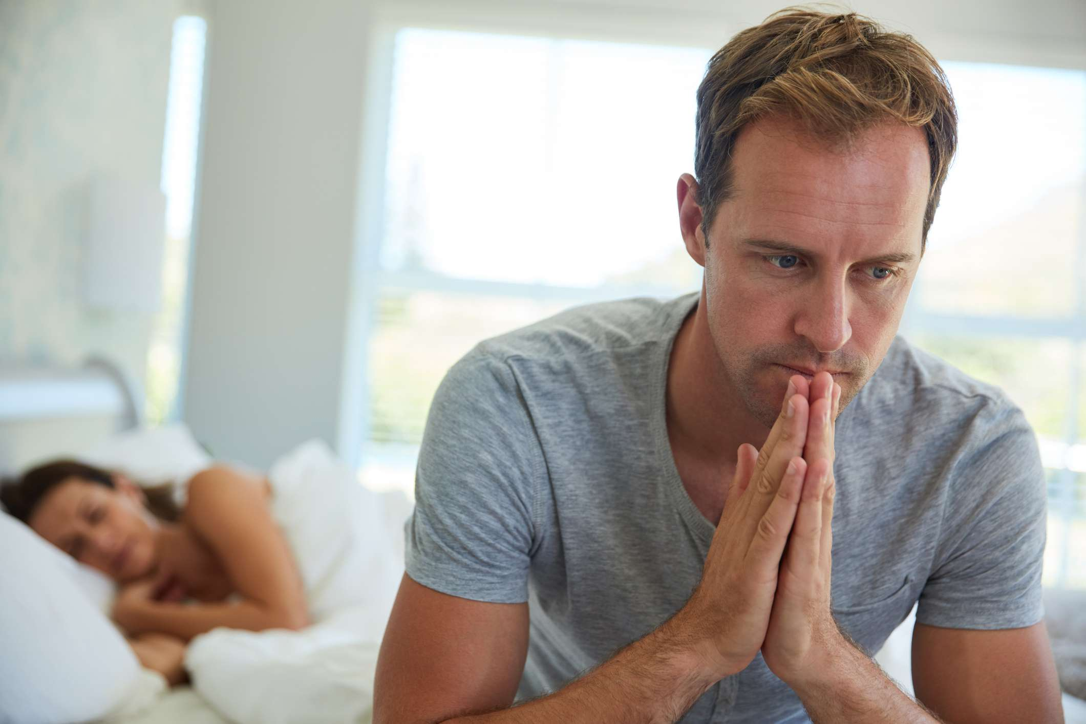 Man looking distressed on edge of bed