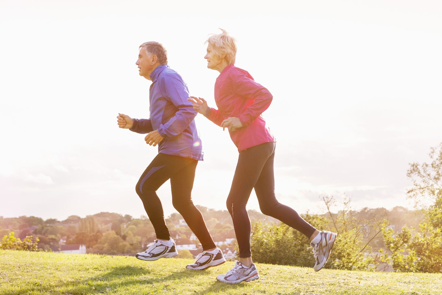 Older couple running in a park to lower high triglycerides
