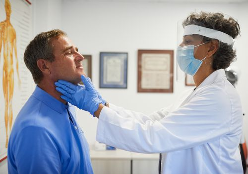 man having his throat checked by female doctor in PPE