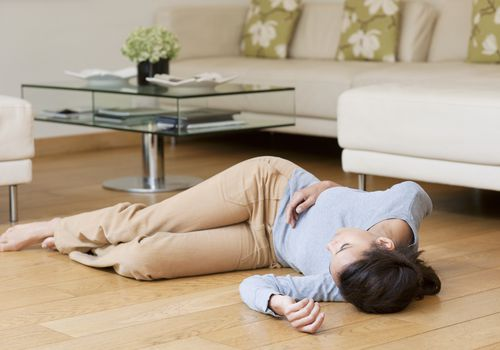 Woman who fainted lying on the floor next to a couch