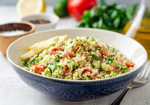 Traditional Arabic Salad Tabbouleh with couscous, vegetables and greens on concrete background
