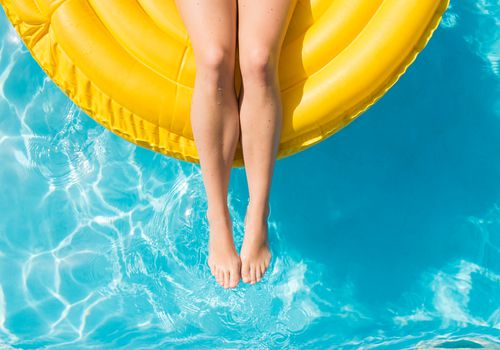 Woman floating on tube in the pool.