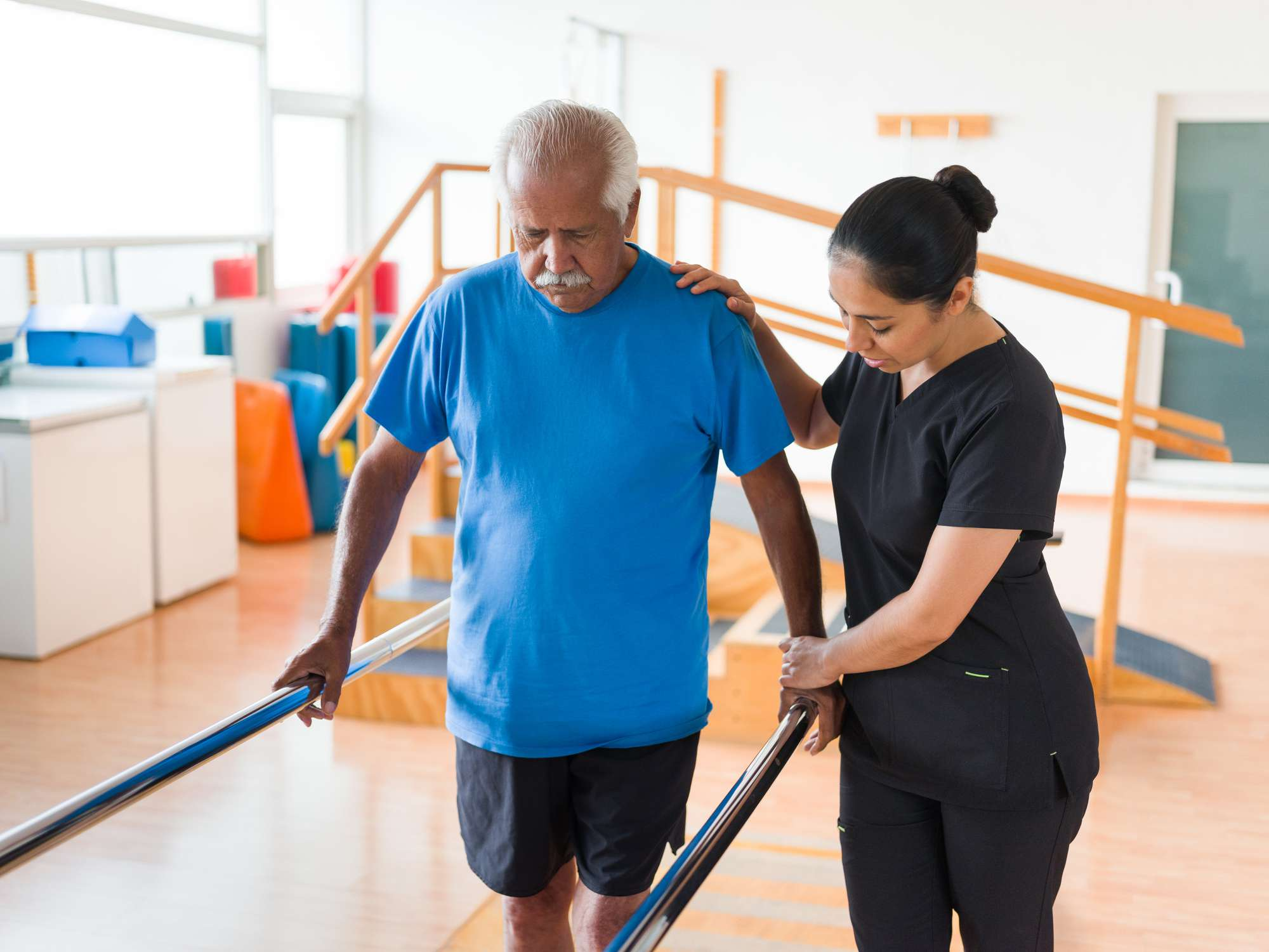 physical therapist assisting elderly man walking in parallel bars