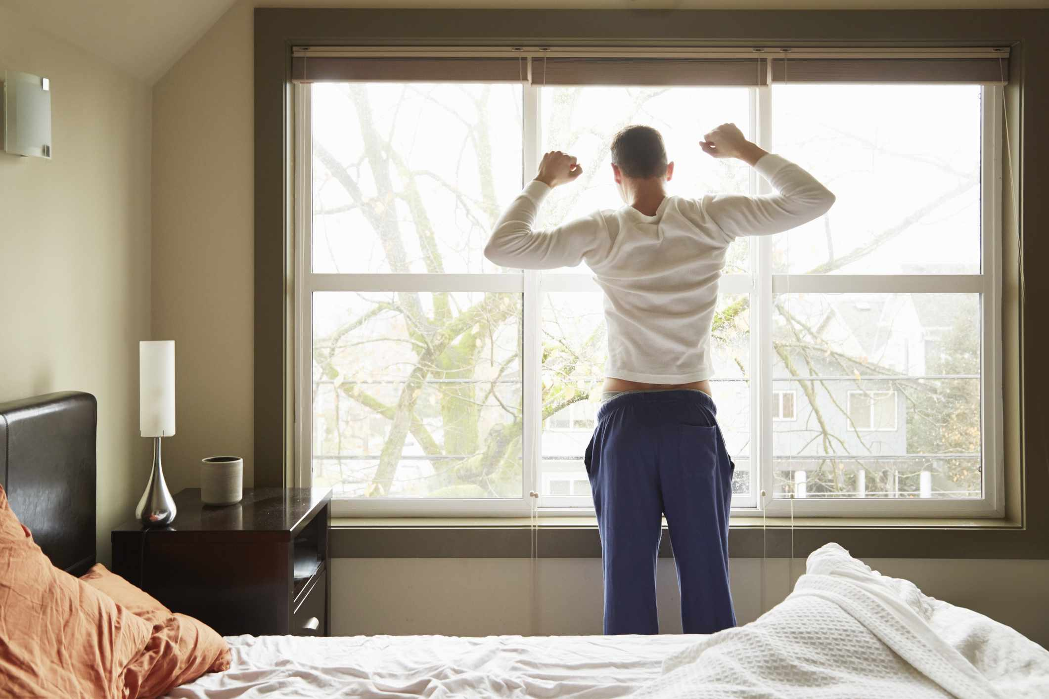 Rear view of young man stretching in the morning