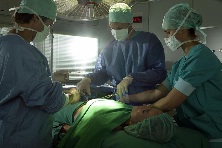 Three surgeons performing surgery