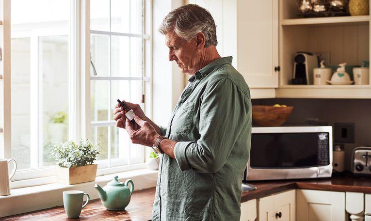 Man looking at CBD oil bottle in kitchen