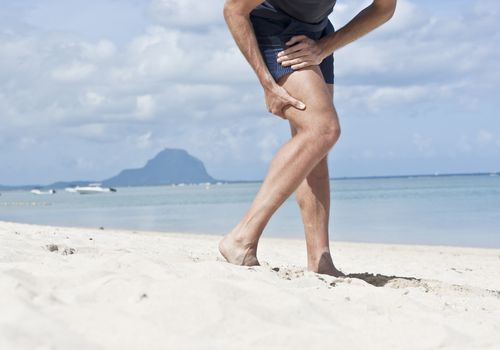 Man on beach with leg injury.