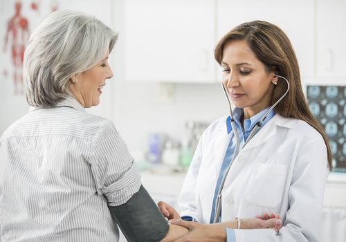 Doctor checking a patient's blood pressure.