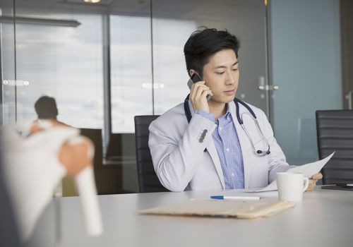 Doctor on the Phone looking at paperwork