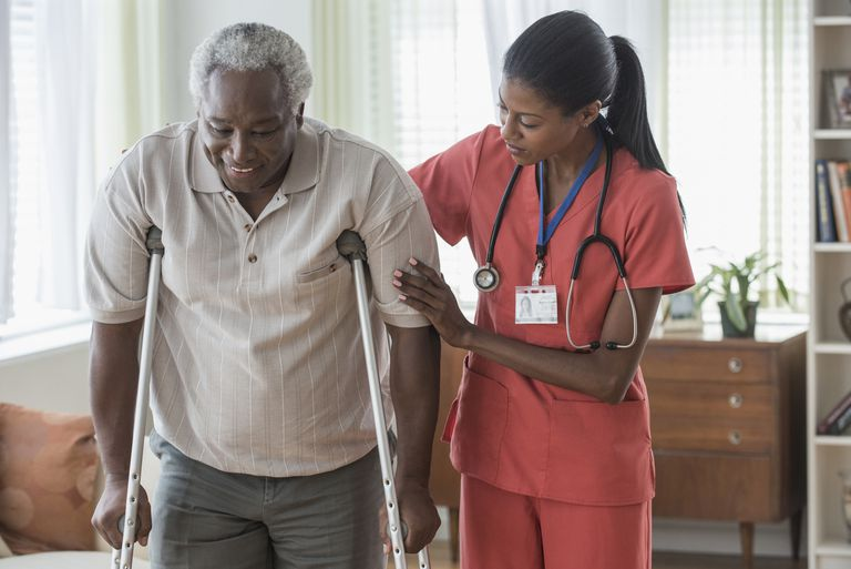 Caregiver helping older man walk on crutches