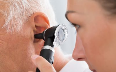 female doctor examining a patient's ear