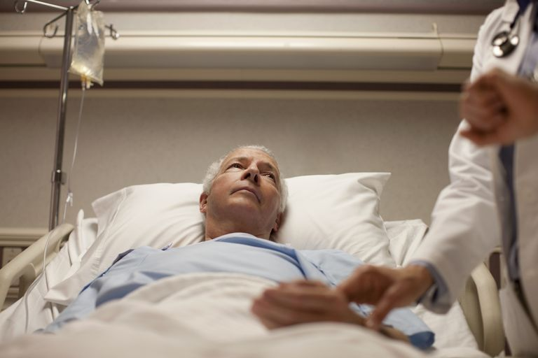 doctor taking pulse of senior man in hospital bed