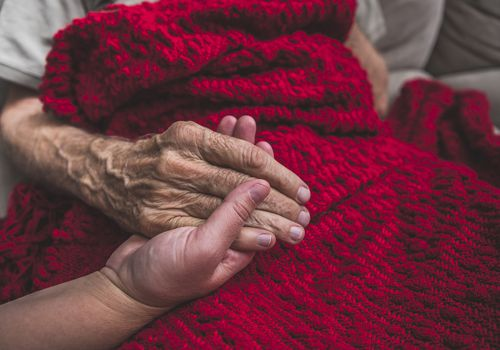 holding elderly hand red blanket