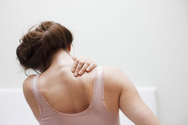 Woman rubbing shoulder and back pain