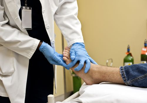 A doctor examining a patients foot
